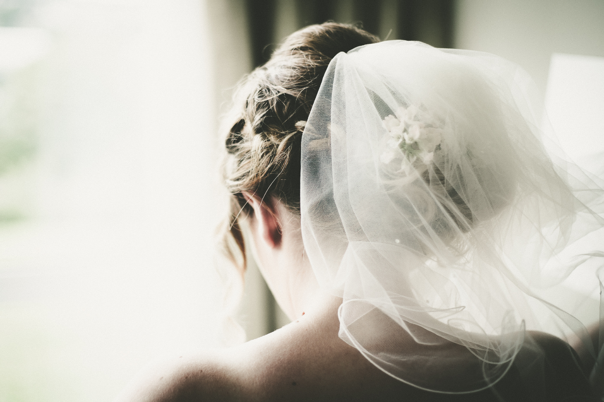 close up shot of back of a bride with veil and hair finished